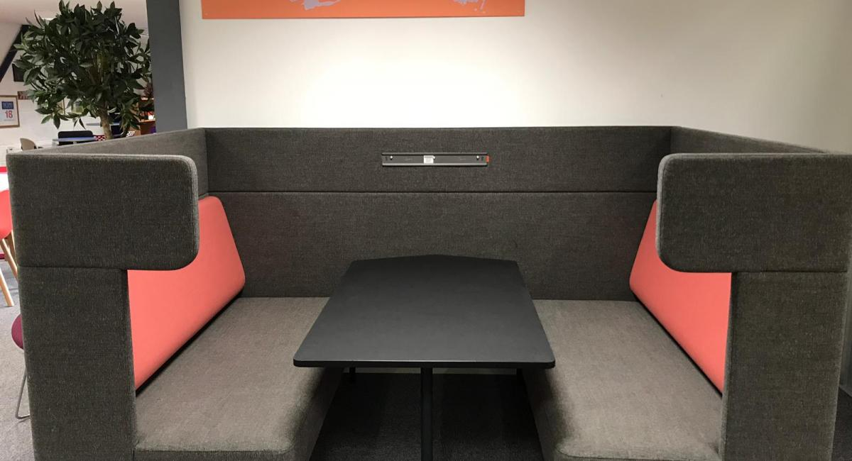 OCEE FourUS Work Booth upholstered in charcoal with red cushioning and black pivot table.