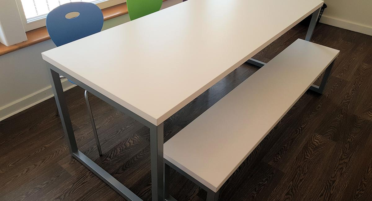 Steel frame bench table finished with a white top, partnered with coloured polypropylene chairs.