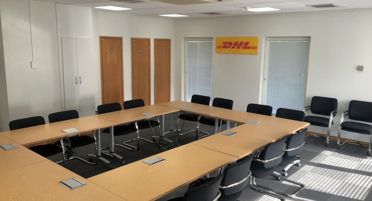 Boardroom furniture refurbishment with tilt top table tops, partnered with black cantilever frame chairs.