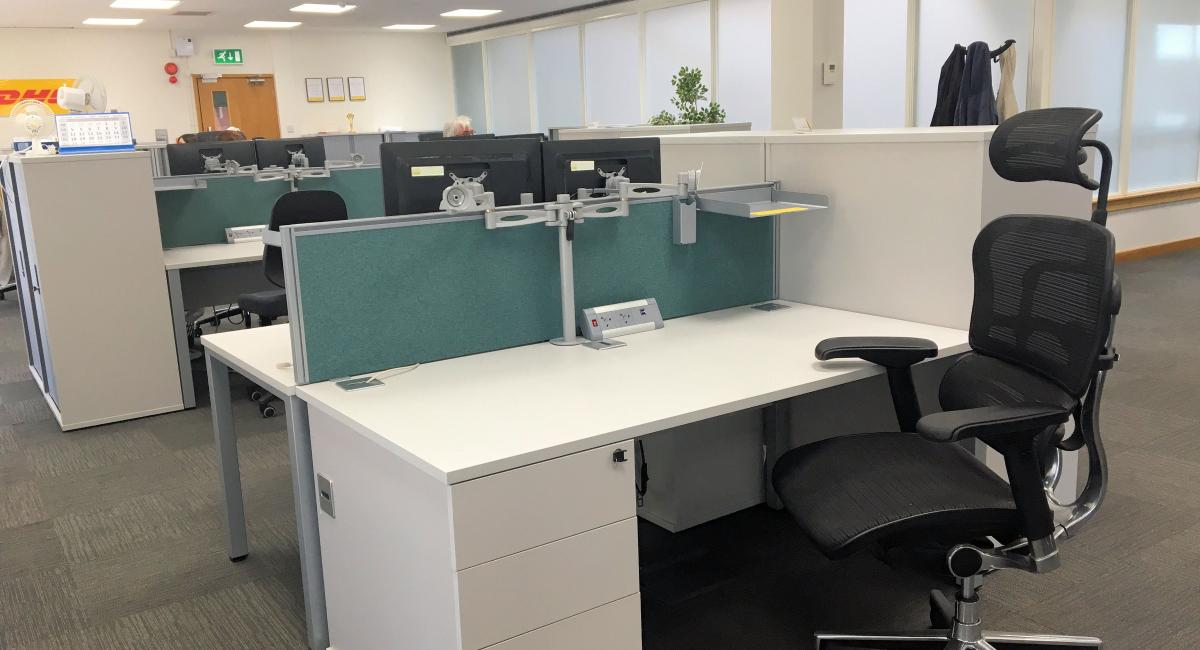 White cantilver frame office desk, partnered with white personal pedestal drawers and black task chairs with headrest and arms.