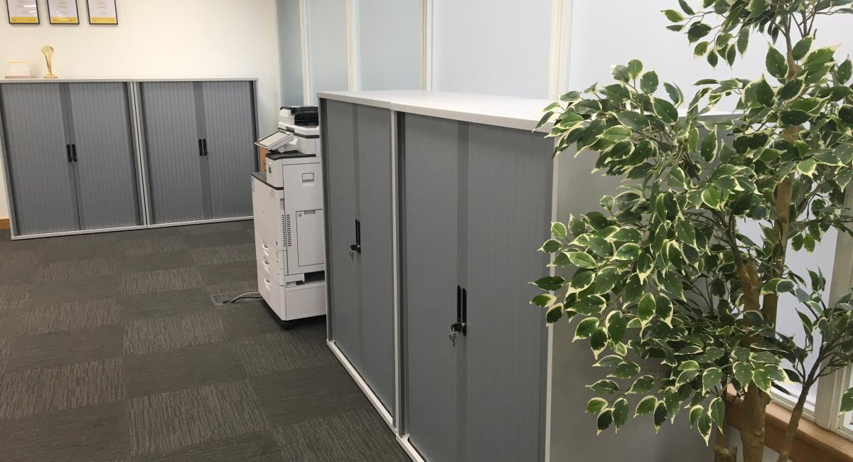 White storage cuboards with silver, side opening and lockable tambour doors.
