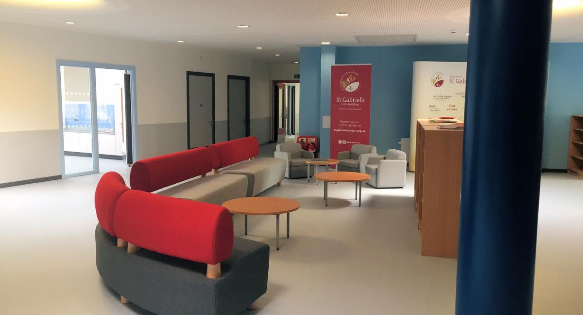 Educational breakout space, with charcoal and burgundy sofa seating and loose furniture.