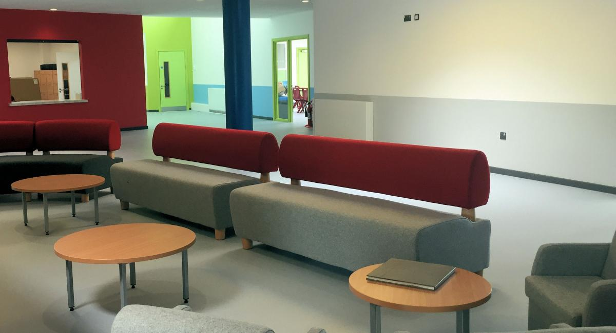 Breakout space furniture including grey and burgundy sofas and loose furniture.