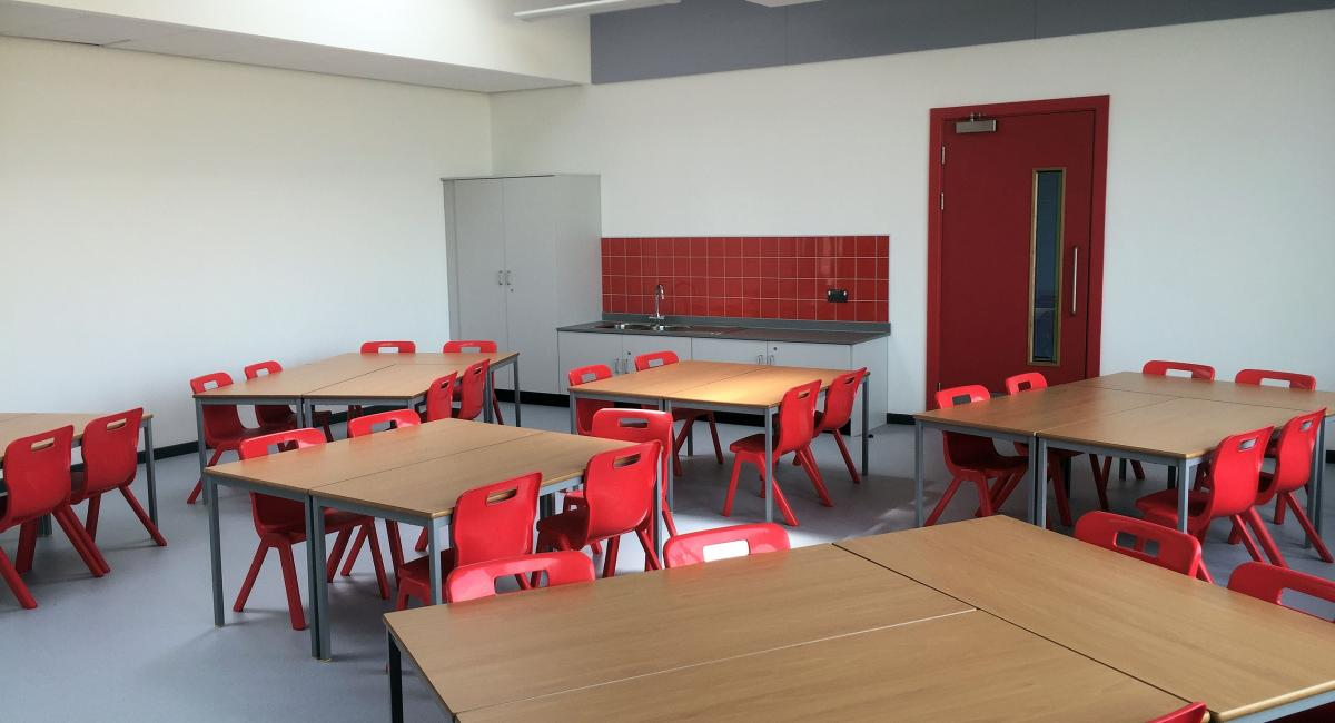 Beech classroom tables partnered with red one-piece Postura+ classroom chairs.