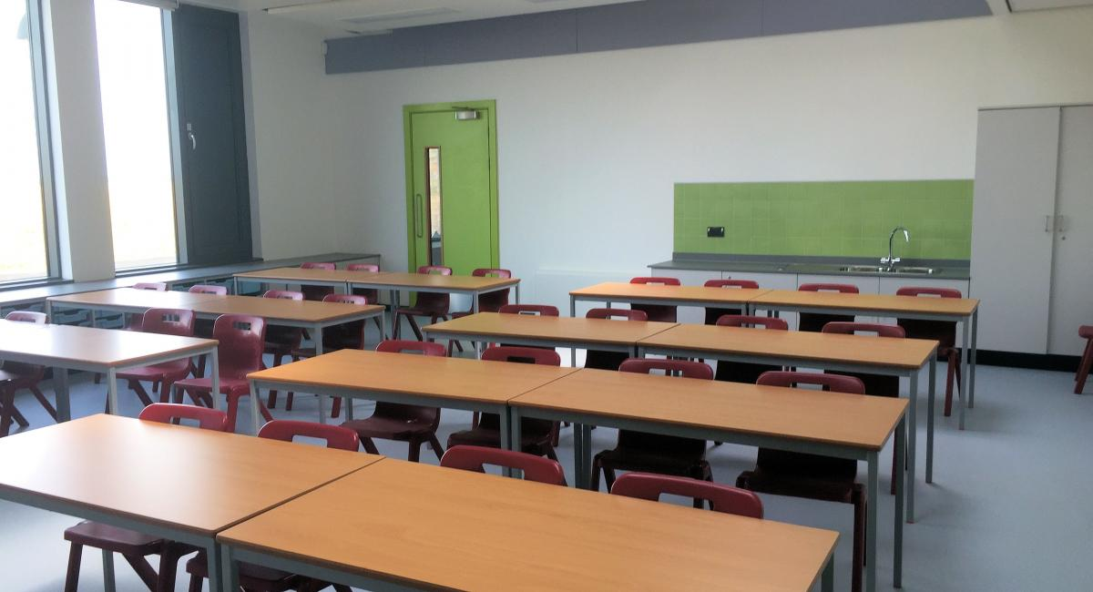 Beech fully welded classroom tables, partnered with red one piece Postura+ classroom chairs.